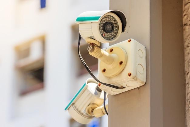 Macchina fotografica o sistema di sorveglianza del cctv di sicurezza in edificio per uffici sul fondo del cielo blu