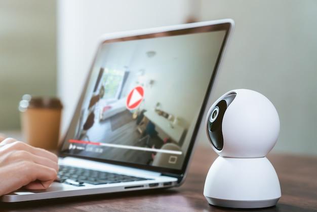 Telecamera tvcc di sicurezza sul tavolo e utilizzo di laptop con registrazione video alla ricerca