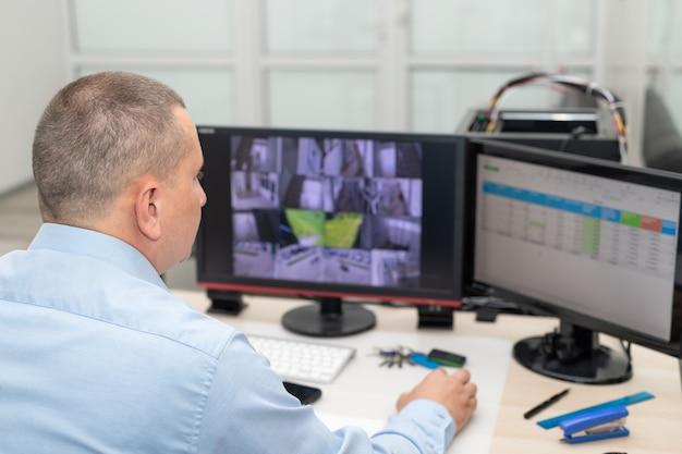 Guardia di sicurezza che monitora le telecamere cctv nella stanza di sicurezza