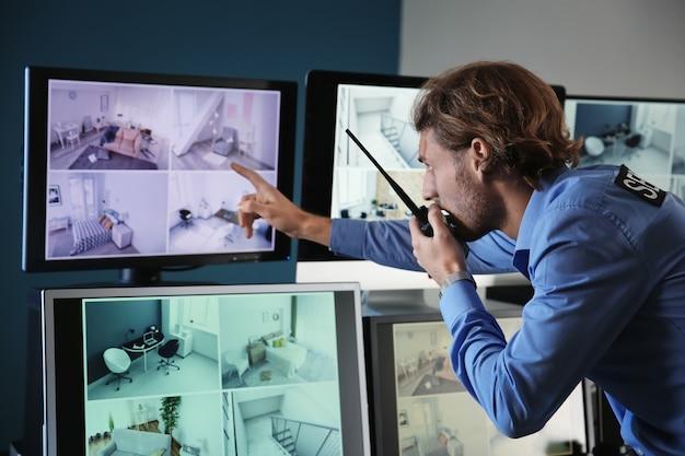 Guardia di sicurezza che controlla le moderne telecamere a circuito chiuso nella sala di sorveglianza