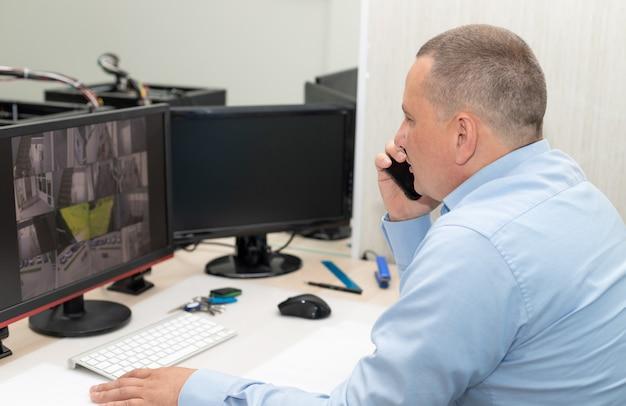 Guardia di sicurezza che guarda le telecamere a circuito chiuso e parla al cellulare