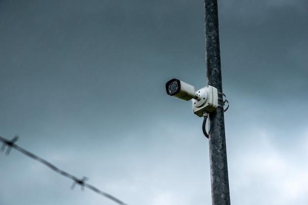Telecamera ir di sicurezza per monitorare gli eventi. telecamera cctv ip sullo sfondo di cielo nuvoloso e pioggia e filo spinato