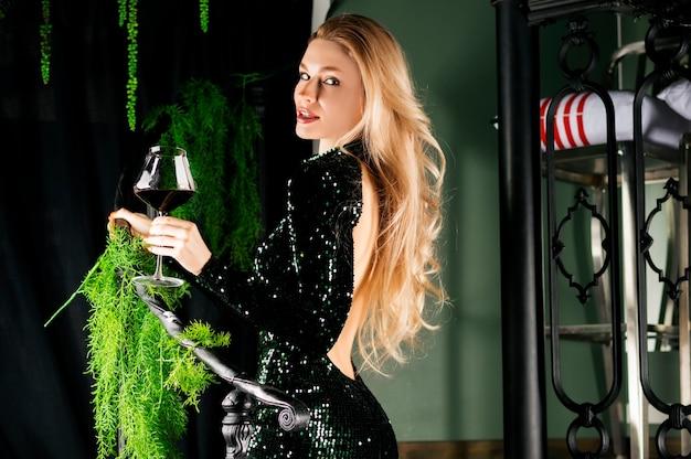 Bionda seducente in un abito da sera verde in posa con un bicchiere di vino rosso.