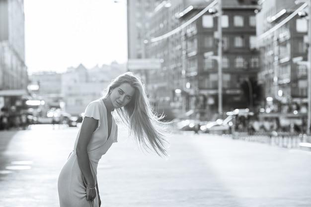 Seducente donna bionda con i capelli lunghi indossa un vestito che cammina in città. tonificazione in bianco e nero. spazio per il testo