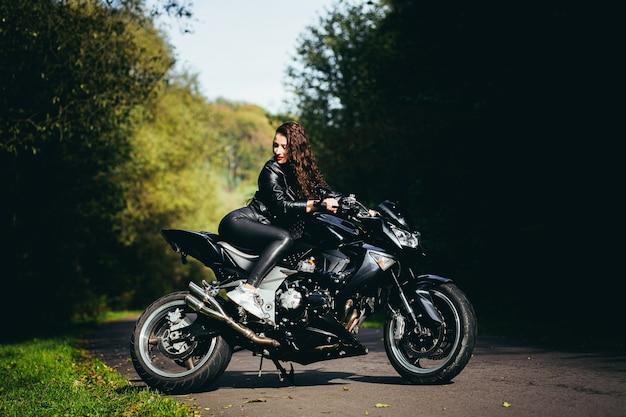 Seducente ragazza bruna con i capelli lunghi in una giacca di pelle nera si siede vicino a una moto moderna su uno sfondo di natura. closeup ritratto di una donna sexy vicino a una costosa bici nera.