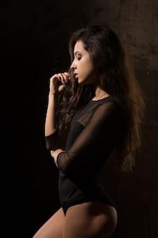 Donna seducente di forma fisica con trucco luminoso in biancheria nera che posa vicino alla parete scura