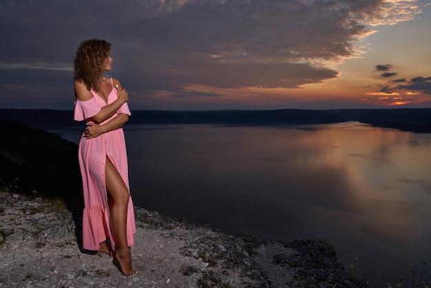 Ragazza seducente su sfondo di cielo notturno e lago.