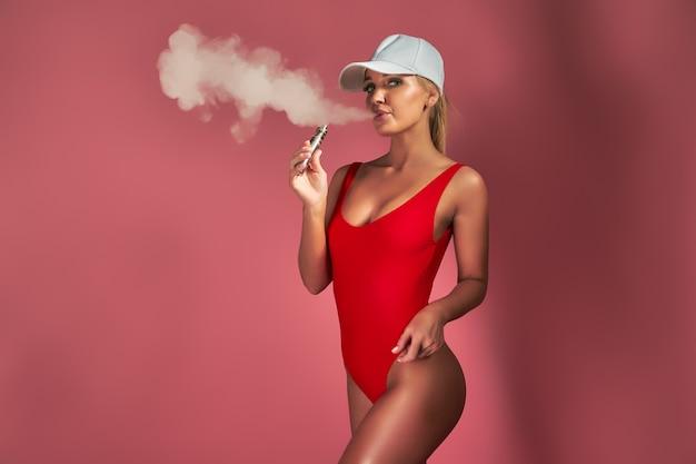 Giovane donna seducente glamour in costume da bagno rosso in piedi e svapare sul rosa