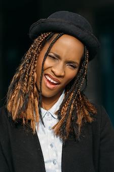 Seducente femmina nera sogghignante. umore giocoso. divertente donna afroamericana su sfondo scuro, vestiti modello alla moda, concetto gioioso