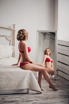 Donna seducente in biancheria rossa luminosa che si siede sul letto contro lo specchio.