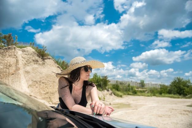 Donna seducente che posa vicino all'automobile in estate fuori città godendo della libertà
