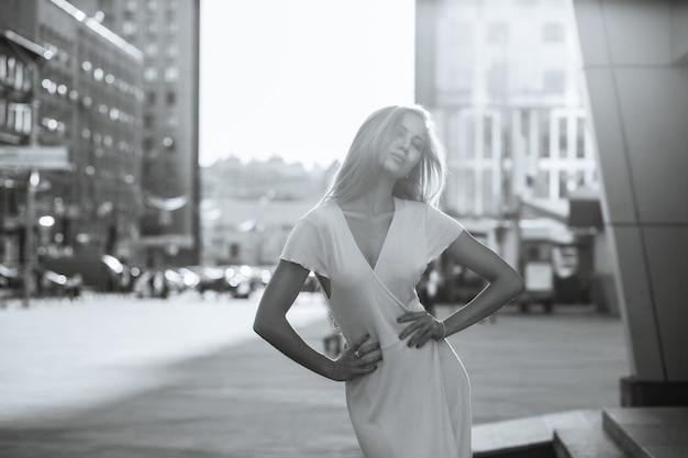 La donna seducente indossa abiti alla moda in posa per strada. spazio per il testo. colore monocromatico