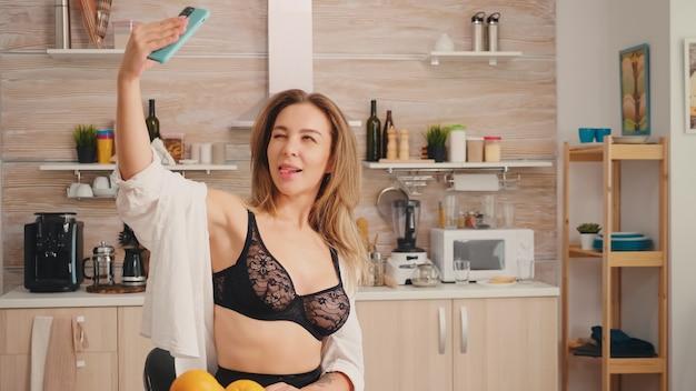 Seducente donna con tatuaggi utilizzando smartphone indossando biancheria intima temping al mattino prendendo selfie sensuale. donna bionda attraente sexy in biancheria nera che tiene telefono cellulare mobile