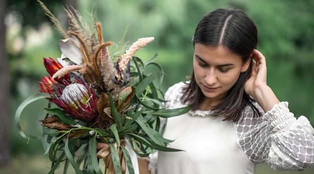 Giovane donna castana seducente in un vestito bianco con un mazzo di fiori nella foresta su un fondo vago,