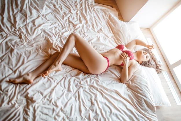 Giovane donna dai capelli scuri nuda seducente sul letto mattina