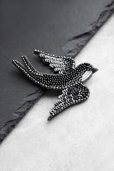 Spilla ricamata con perline a forma di uccello rondine nero su sfondo nero