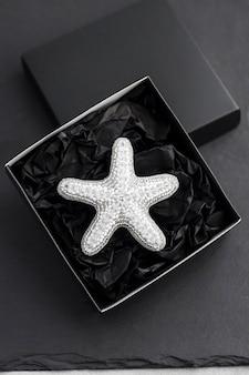 Spilla ricamata con perline a forma di stella marina in scatola nera su sfondo nero