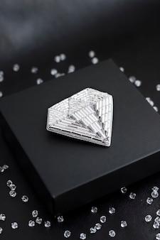 Spilla ricamata con perline di semi a forma di diamante su scatola regalo nera su superficie nera