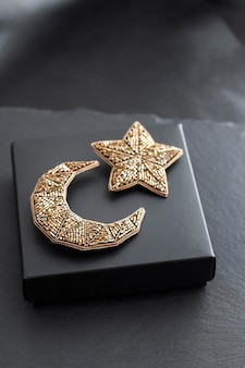 Spille ricamate con perline a forma di luna e stella su sfondo scatola nera
