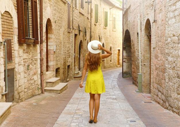Visto da dietro della donna turistica in abito giallo e cappello in visita alla vecchia città italiana.