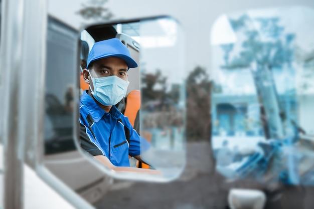 Visto dalla finestra di un autista maschio in uniforme e con indosso una maschera che guarda la telecamera mentre è seduto sull'autobus