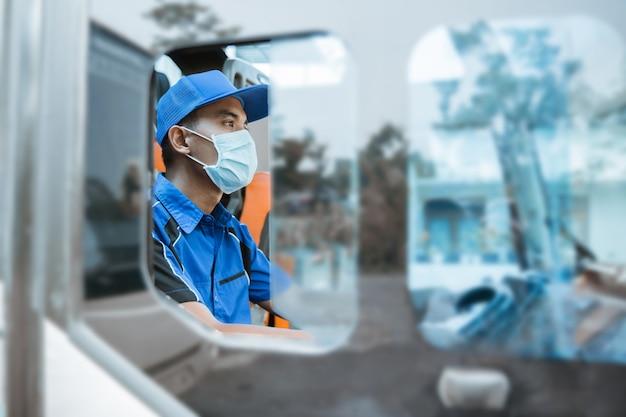 Visto dal finestrino di un autista maschio in uniforme e con indosso una maschera mentre è al volante sull'autobus