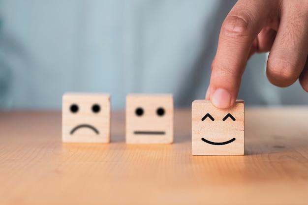 Seleziona il concetto di emozione o umore, mano che tiene la faccia sorridente o la faccia felice che stampa la schermata sul blocco di cubo di legno.