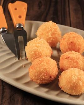 Selected focus arancini/pallina di riso/nugget rotonda ricoperta di pangrattato, pronti per friggere. preparazione della cottura in cucina