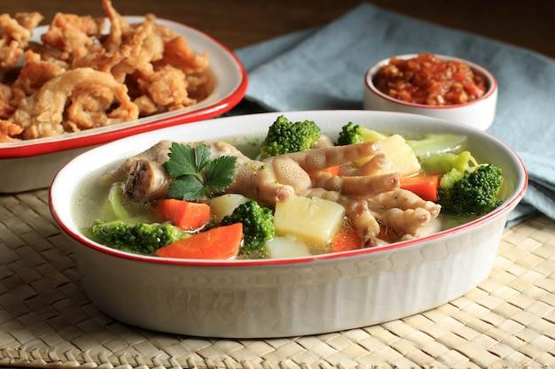 Selected focus piedi di pollo (ceker) su zuppa chiara di verdure con patate, broccoli e carote. servito su un tavolo di legno in una ciotola ovale con sambal. e funghi ostrica copia spazio per il testo