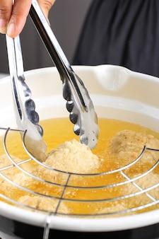 Processo di cottura selezionato: mano femminile asiatica tenere pinze in acciaio inossidabile in padella fritta, friggere bakso goreng o pollo fritto o polpette di gamberetti