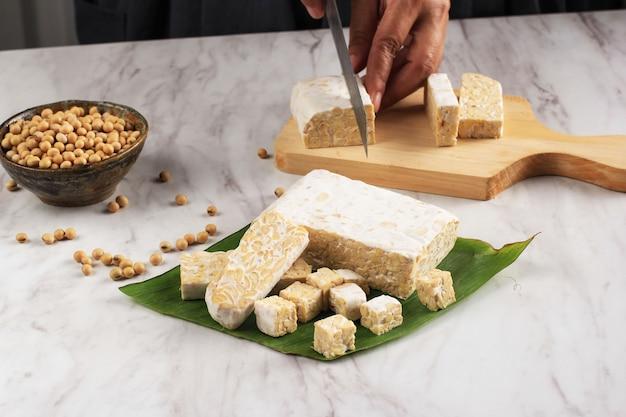 Messa a fuoco selezionata a mano femminile per affettare tempeh o tempe sul tagliere di legno usando il coltello. tempe è un prodotto di soia fermentata originario dell'indonesia.