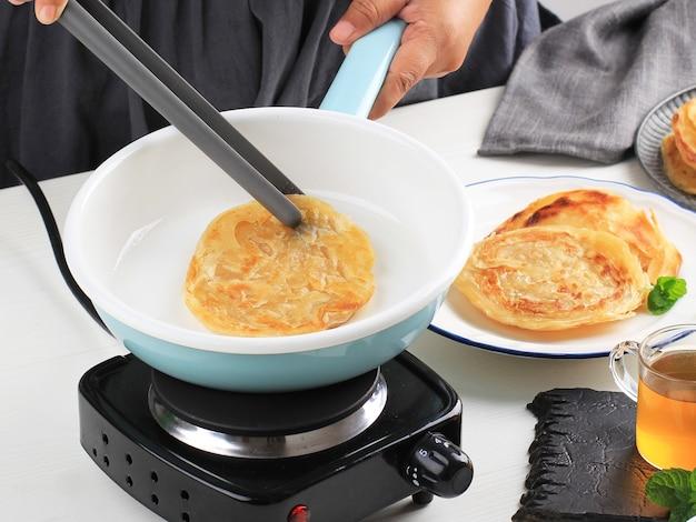 Focus selezionato donna femminile che cucina il pane piatto di canai o paratha del medio oriente, o anche conosciuto come roti maryam in indonesia. processo di cottura su sfondo bianco in cucina