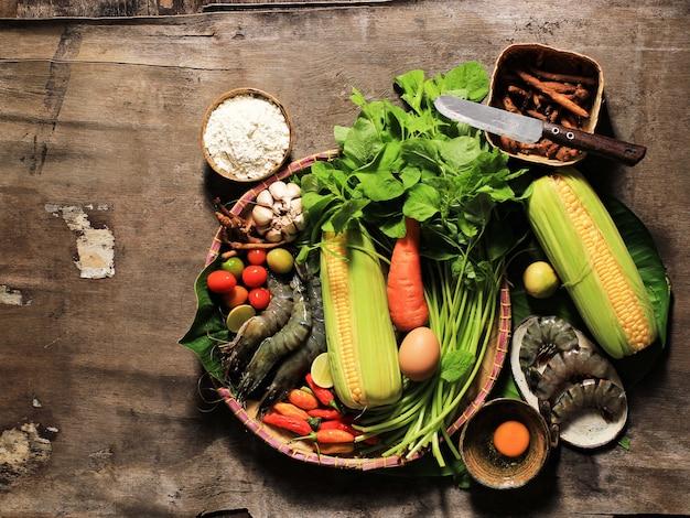 Messa a fuoco selezionata flatlay cooking ingredienti preparazione, preparazione di zuppa di spinaci (sayur bayam) e tempura di gamberi. composizione di ingredienti freschi crudi con copia spazio per testo o pubblicità