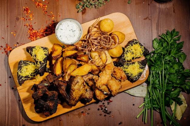 Selezione di birra e snack. patatine, pesce, salsicce di birra sul tavolo. vista dall'alto