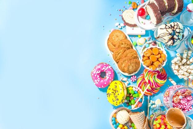 Selezione di dolci colorati. set di varie caramelle, cioccolatini, ciambelle, biscotti, lecca-lecca, gelato vista dall'alto su sfondo blu brillante alla moda
