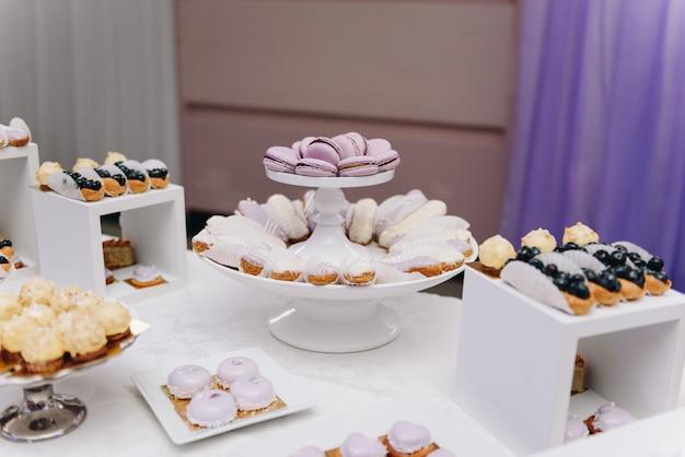 Selezione di deliziosi dessert, torte, cupcakes e pasticceria su un tavolo da buffet al banchetto