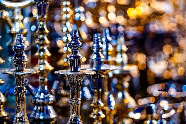 Selezione di diverse ciotole di narghilè metalliche in vetrina nel negozio di souvenir su sfondo sfocato