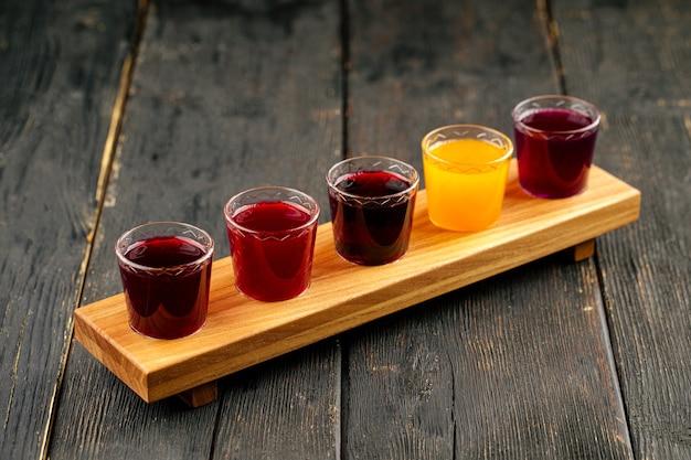 Selezione di diversi colpi di tintura alcolica di frutta naturale su fondo di legno nero