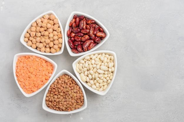 Selezione di legumi secchi, lenticchie e piselli in ciotole bianche su sfondo grigio cemento.
