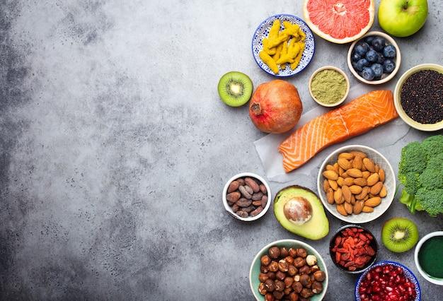 Selezione di prodotti sani e supercibi: salmone, frutta, verdura, frutti di bosco, goji, spirulina, matcha, quinoa, chia, noci con copia spazio. concetto di cibo pulito, sfondo grigio, vista dall'alto, primo piano