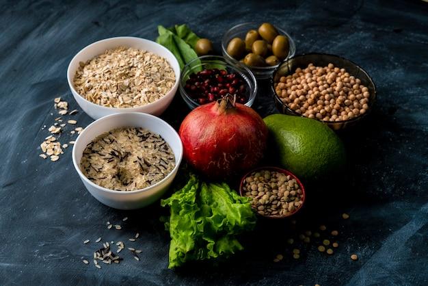 Selezione di superfood sano sulla superficie della lavagna con cereali di frutta ed erbe aromatiche