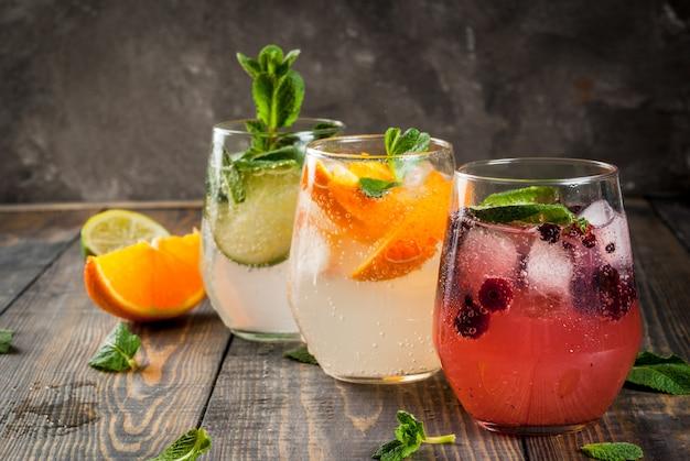 Selezione di tre tipi di gin tonic: con more all'arancia con lime e foglie di menta. in bicchieri su uno sfondo di legno rustico.
