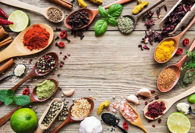 Una selezione di varie spezie colorate su un tavolo di legno in cucchiai