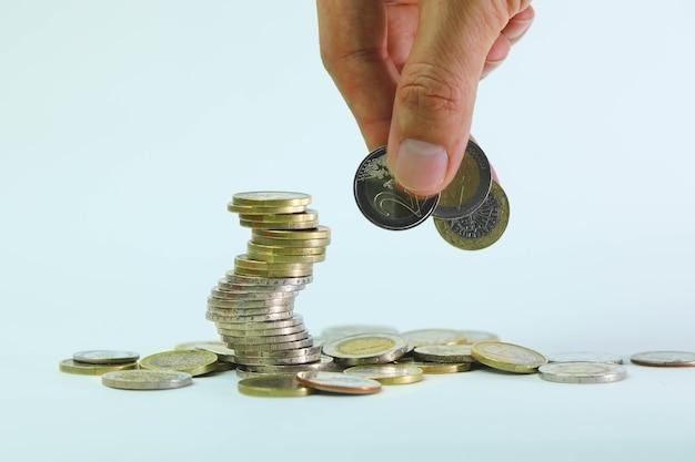 Messa a fuoco selettiva su monete da 2 euro. mano che tiene 2 monete in euro su sfondo bianco