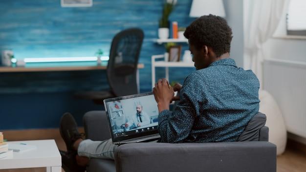 Messa a fuoco selettiva sul paziente afroamericano a casa in cerca di aiuto medico dal medico tramite consultazione online di telemedicina intenet con il medico di famiglia. checkup sanitario tramite videoconferenza virtuale
