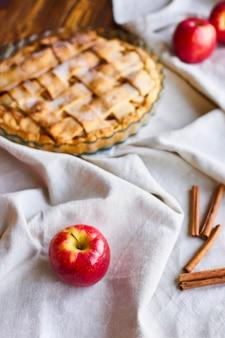Messa a fuoco selettiva su apple. composizione della torta di mele saporita casalinga sulla tavola di legno con le mele crude e l'asciugamano di tela su fondo di legno