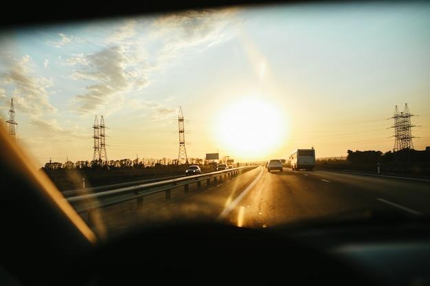 Messa a fuoco selettiva strada asfaltata attraverso il vetro del vento, guidando un'auto al tramonto. sfondo di viaggio