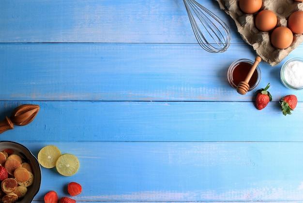Messa a fuoco selettiva sfondo di cottura con ingredienti di cottura come uova, fragole, limone, zucchero dus e miele. adatto per sfondo o carta da parati su sfondo blu in legno