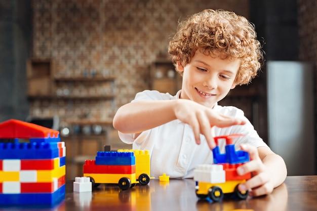 Messa a fuoco selettiva su un bambino raggiante seduto a un tavolo e sorridente mentre trascorre il suo tempo libero a casa e si diverte con un set di costruzioni.