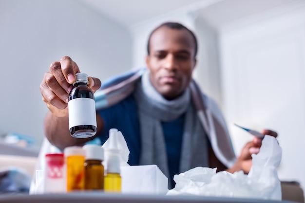 Messa a fuoco selettiva di una bottiglia con sciroppo per la tosse prelevata dal tavolo da un simpatico uomo malato piacevole